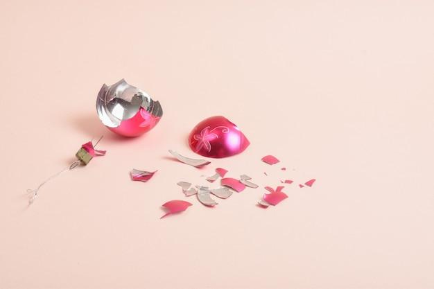 Rozbita szklana bombka na różowym tle. zepsuta świąteczna zabawka.