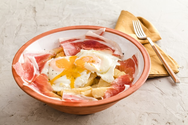 Rozbite jajka sadzone z ziemniakami i iberyjską szynką w hiszpańskiej restauracji