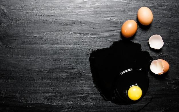 Rozbite jajko. na czarnym drewnianym stole. wolne miejsce na tekst. widok z góry
