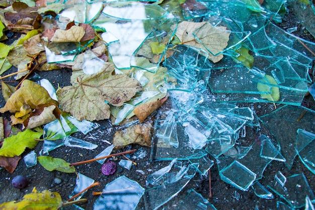 Rozbite szkło na podłodze ulicy i jesienne liście