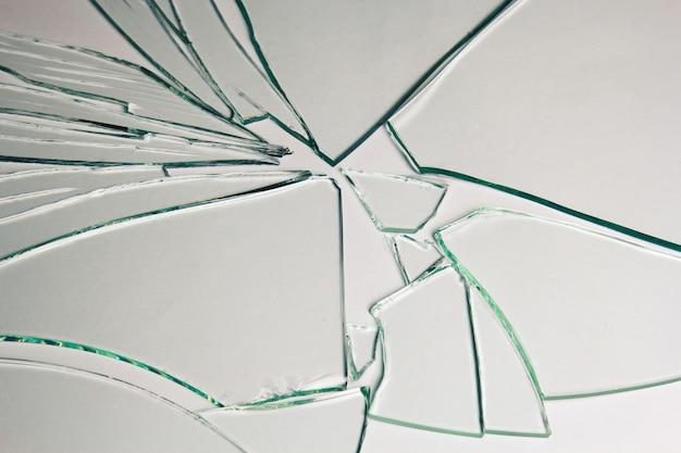 Rozbite szkło stos kawałków tekstury i tła na białym, efekt krakowanego okna. stan awaryjny.