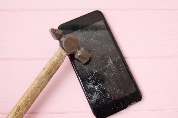 Rozbity ekran telefonu na stole młotkiem