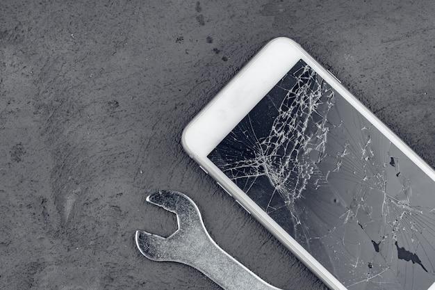 Rozbity smartfon z narzędziami do naprawy na szarej powierzchni
