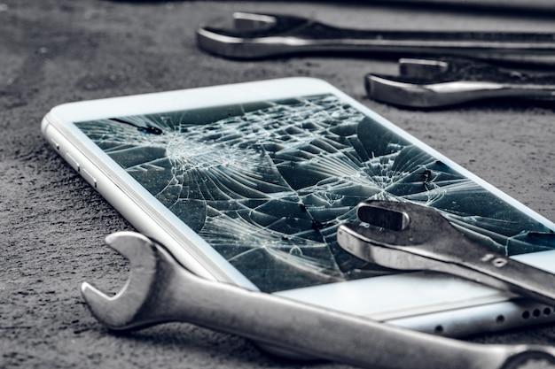 Rozbity smartfon z narzędziami do naprawy na szaro