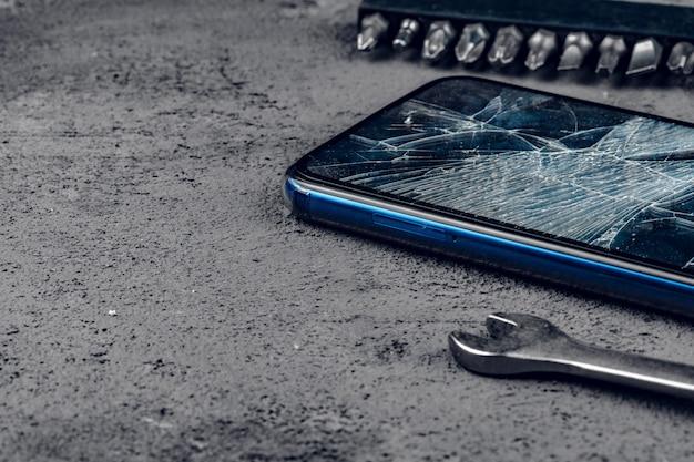 Rozbity smartfon z narzędziami do naprawy