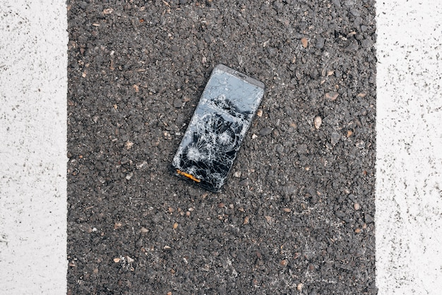 Rozbity telefon leżący na środku ulicy