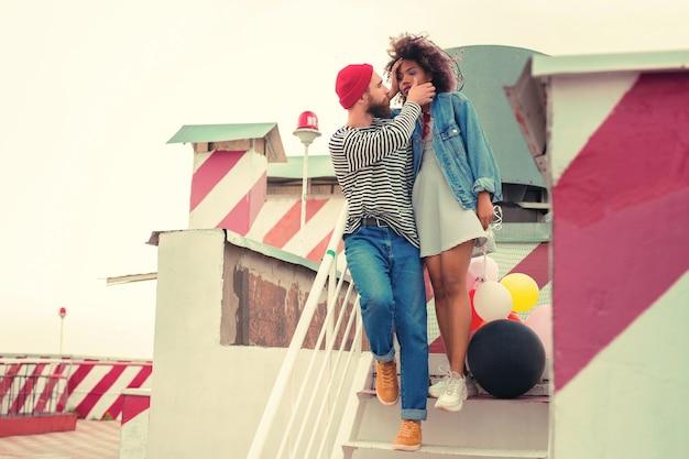 Rozchmurz się. kochający młody człowiek delikatnie dotyka twarzy swojej śpiącej dziewczyny stojąc z nią na schodach po imprezie