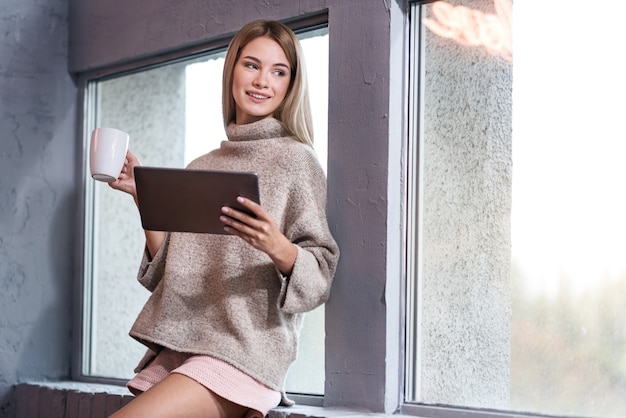 Rozchmurz się. piękna młoda kobieta zachwycona za pomocą tabletu i picia kawy, uśmiechając się rano.