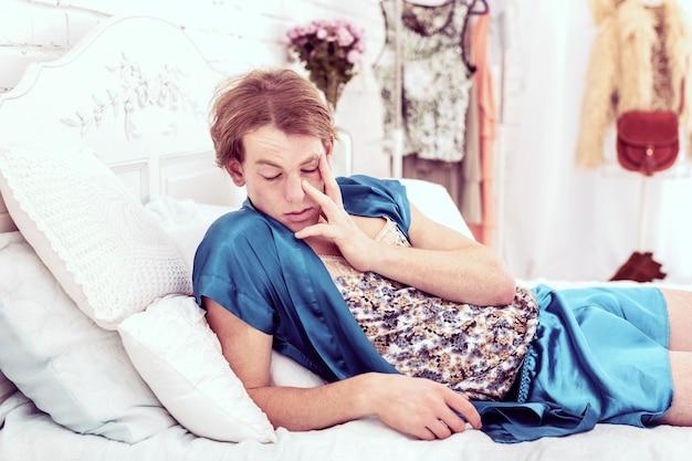 Rozciągając się. zmęczony, krótkowłosy mężczyzna budzi się i czuje się zmęczony, wstając z wygodnego białego łóżka