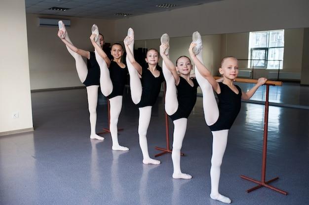 Rozciąganie, dzieci na lekcji tańca baletowego.