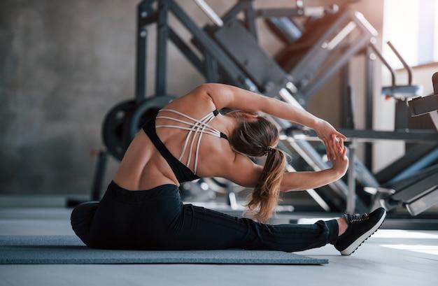 Rozciąganie jogi. zdjęcie pięknej blondynki na siłowni w czasie weekendu