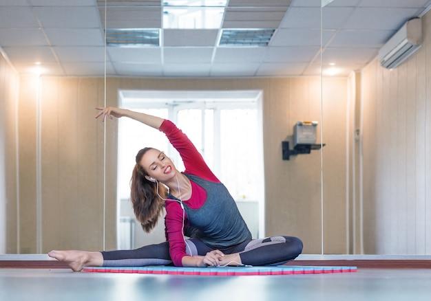 Rozciąganie młoda kobieta z słuchawkami. trening pilates w domu
