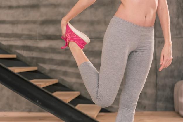 Rozciąganie nóg. szczupła kobieta ubrana w szare legginsy i jasnoróżowe trampki rozciągające nogi po fitnessie