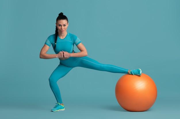 Rozciąganie. piękna młoda lekkoatletka praktykujących, monochromatyczny niebieski portret. sportowy dopasowany model brunetka z fitballem. koncepcja budowy ciała, zdrowego stylu życia, piękna i działania.