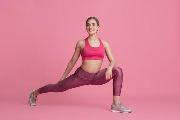 Rozciąganie. piękna młoda lekkoatletka praktykujących, monochromatyczny różowy portret. trening sportowego modelu kaukaskiego. koncepcja budowy ciała, zdrowego stylu życia, piękna i działania.