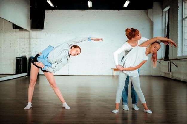 Rozciąganie. profesjonalna nauczycielka tańca nowoczesnego z rudymi włosami, ubrana w białą koszulkę, pomagająca jej uczniowi się rozciągać