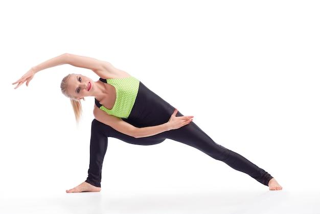 Rozciąganie przed siłownią. piękna, wesoła kobieta uśmiecha się podczas rozciągania przed ćwiczeniem na białym tle copyspace sportowa koncepcja aktywności witalności siłowni