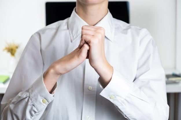 Rozciąganie ramion w rzadkim miejscu pracy w biurze. ręce pracownika przed nowoczesnym pulpitem, zmęczony pisaniem koncepcji