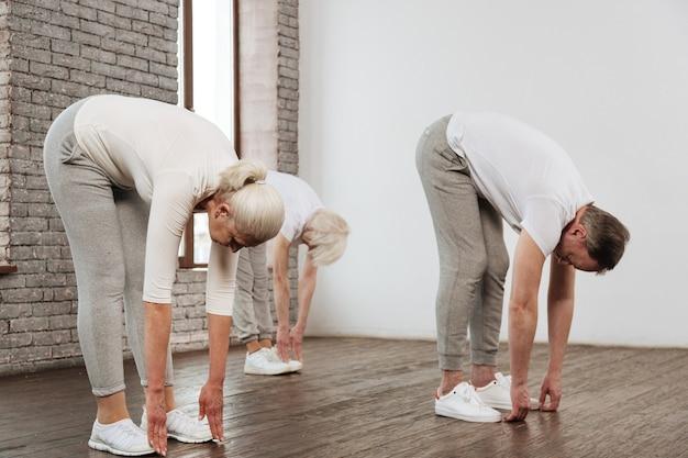 Rozciągnij plecy. trzech przyjaciół w białych tenisówkach stojących w półpozycji, dotykając drewnianej podłogi