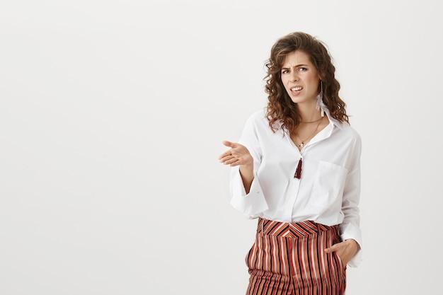 Rozczarowana atrakcyjna kobieta, wskazując ręką z konsternacją i grymasem