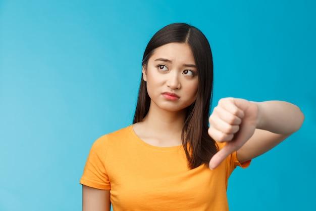Rozczarowana azjatycka gość daje negatywną opinię, odwraca wzrok zaniepokojony i zdenerwowany, pokazuje znak niechęci kciukiem w dół, ocenia złe rzeczy, słabą jakość, stoi na niebieskim tle. skopiuj miejsce