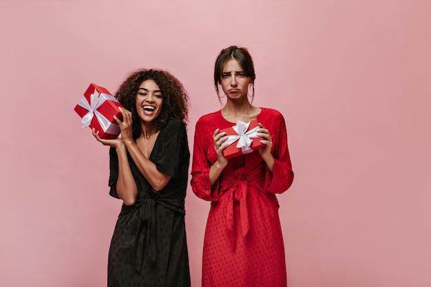 Rozczarowana dama z kolczykami w fajnych ciuchach w kropki trzymająca pudełko prezentowe i pozująca z radosną dziewczyną z kręconymi brunetami