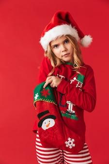 Rozczarowana dziewczynka ubrana w świąteczny kostium stoi na białym tle, biorąc prezenty ze świątecznej skarpety