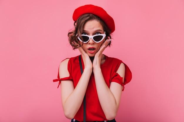Rozczarowana francuska modelka pozuje w okularach przeciwsłonecznych. nieszczęśliwa krótkowłosa kobieta w czerwonym berecie na białym tle.