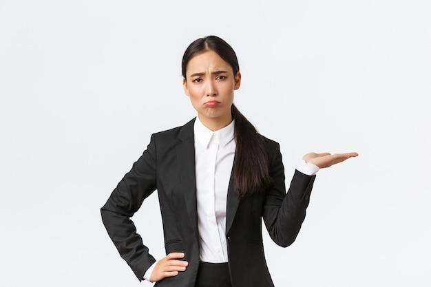 Rozczarowana i posępna kierownik sprzedaży, agentka nieruchomości w czarnym garniturze mająca zły dzień, dąsająca się i wyglądająca na zdenerwowaną, pokazując coś, trzymająca rękę w prawo, białe tło
