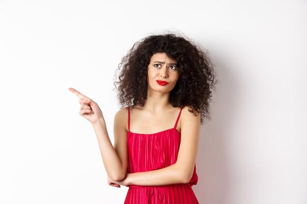 Rozczarowana I Sceptyczna Młoda Kobieta Z Kręconymi Włosami, Ubrana W Czerwoną Sukienkę, Krzywiąca Się I Wskazująca Palcem W Lewo Przy Logo, Stojąca Na Białym Tle. Premium Zdjęcia