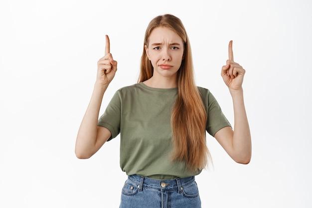 Rozczarowana klientka, wskazująca w górę i uśmiechnięta niezadowolona, nie lubi produktu na wierzchu, wyglądająca sceptycznie, stojąca przy białej ścianie