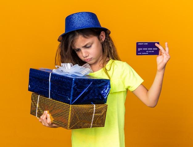 Rozczarowana mała kaukaska dziewczynka w niebieskim kapeluszu imprezowym trzymająca pudełka na prezenty i kartę kredytową odizolowaną na pomarańczowej ścianie z miejscem na kopię