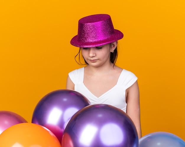 Rozczarowana młoda kaukaska dziewczyna w fioletowym kapeluszu imprezowym, patrząca na balony z helem odizolowane na pomarańczowej ścianie z miejscem na kopię
