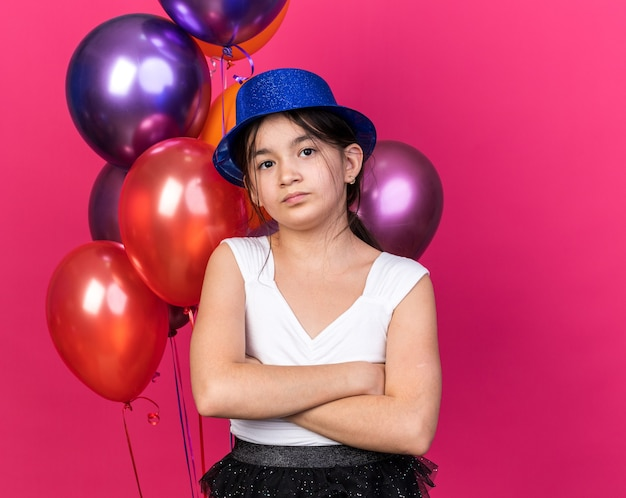 Rozczarowana młoda kaukaska dziewczyna w niebieskim kapeluszu imprezowym stojąca ze skrzyżowanymi rękami przed balonami z helem odizolowanych na różowej ścianie z kopią przestrzeni