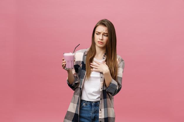 Rozczarowana młoda kobieta pije sok smoothie