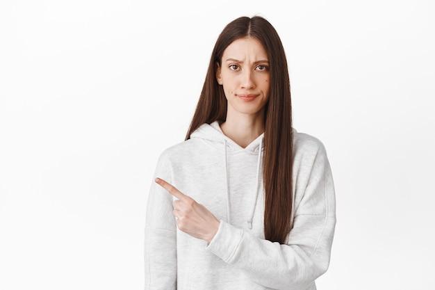 Rozczarowana młoda kobieta wygląda z powątpiewaniem, unosi brew sceptycznie i wskazuje na bok, pokazuje coś złego, nie lubi i ocenia promo, stojąc nad białą ścianą