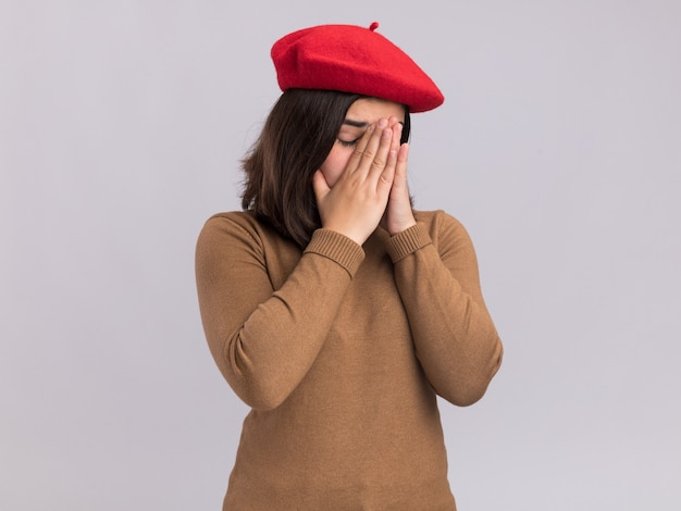 Rozczarowana młoda ładna kaukaska dziewczyna w berecie kładzie ręce na nosie na białej ścianie z miejscem na kopię