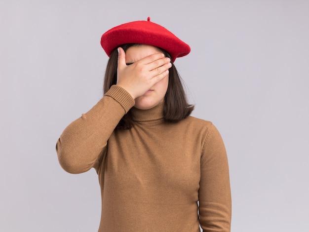 Rozczarowana młoda ładna kaukaska dziewczyna w berecie kładzie rękę na twarzy