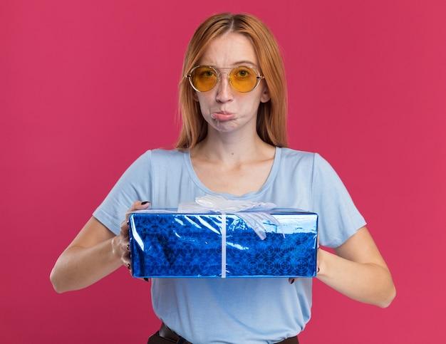 Rozczarowana młoda rudowłosa dziewczyna z piegami w okularach przeciwsłonecznych trzymająca pudełko na prezent