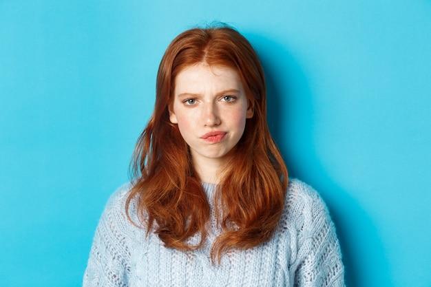 Rozczarowana nastolatka o rudych włosach, marszcząca brwi i niezadowolona, wyglądająca krytycznie, stojąca na niebieskim tle.