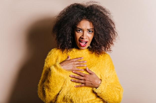 Rozczarowana pani w żółtym swetrze patrząc do przodu