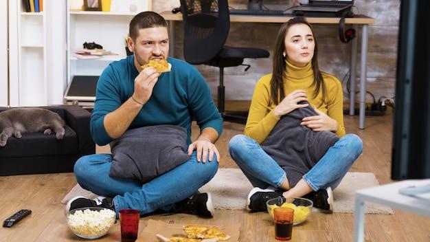 Rozczarowana para siedzi na podłodze, oglądając sport w telewizji i jedząc pizzę ze śpiącym kotem.