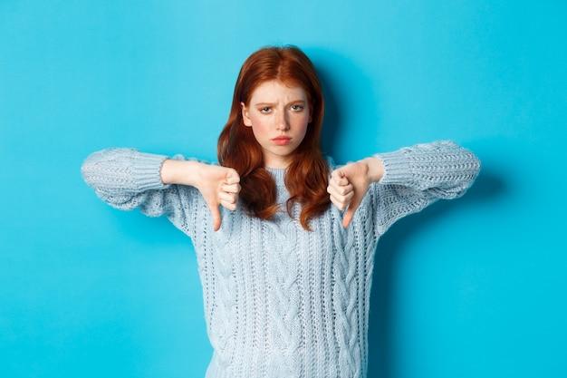 Rozczarowana rudowłosa dziewczyna w swetrze ze skierowanymi w dół kciukami, oceniająca zły produkt, nie zgadzająca się i nie lubiąca promocji, stojąca na niebieskim tle.