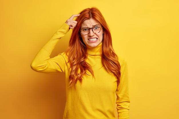 Rozczarowana rudowłosa młoda kobieta ma wątpliwości, że drapie się po głowie i zaciska zęby, nosi zwykły golf, ma złą pamięć.