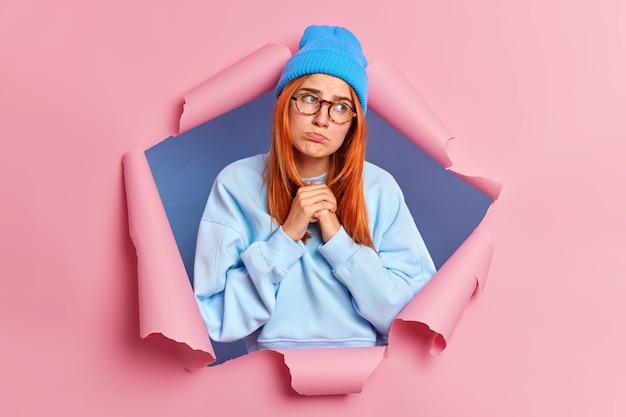 Rozczarowana smutna kobieta trzyma ręce razem, zaciska usta i patrzy zdenerwowana, splata dłonie z frustracją, nosi niebieski sweter, a kapelusz przebija się przez papier