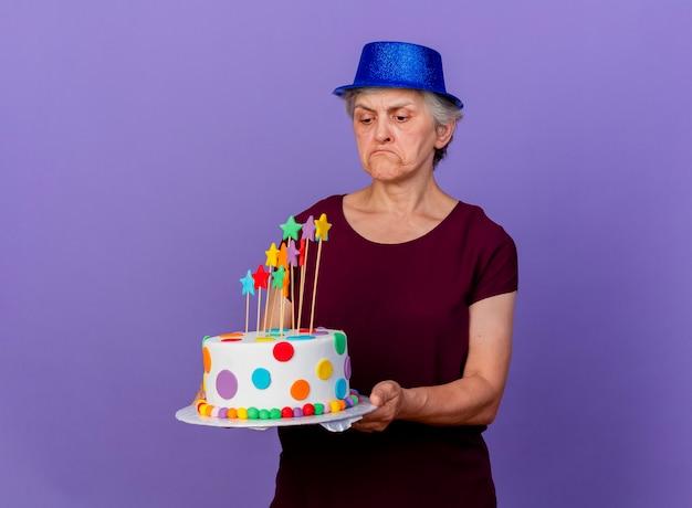Rozczarowana starsza kobieta w kapeluszu imprezowym trzyma i patrzy na tort urodzinowy na białym tle na fioletowej ścianie z miejsca na kopię