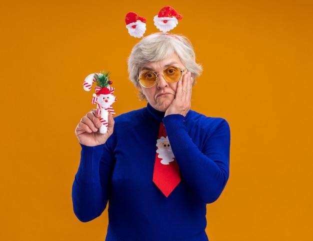 Rozczarowana starsza kobieta w okularach przeciwsłonecznych z opaską świętego mikołaja i krawatem mikołaja kładzie rękę na twarzy i trzyma cukierkową laskę odizolowaną na pomarańczowym tle z miejscem na kopię