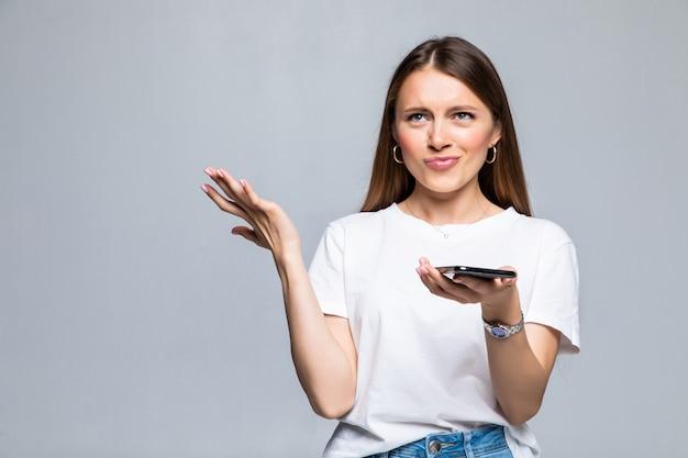 Rozczarowana zdezorientowana kobieta za pomocą smartfona na białym tle