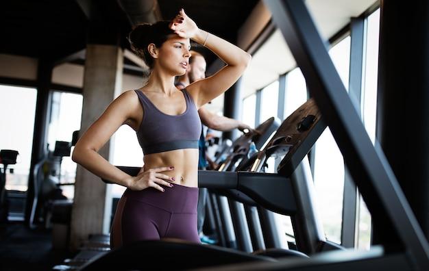 Rozczarowana zmęczona kobieta próbująca osiągnąć cele fitness poprzez trening wytrzymałościowy i wytrzymałościowy na siłowni