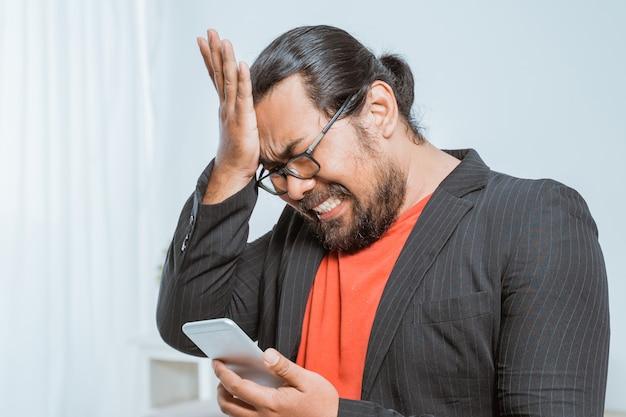 Rozczarowanego biznesmena odbiorcza wiadomość tekstowa na jego smartphone